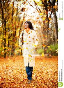 Woman walking outdoors amongst autumn falling leaves